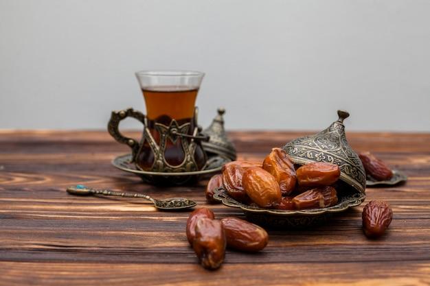お茶のグラスと皿の上のドライ日付フルーツ
