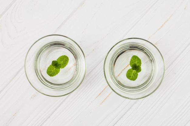 白いテーブルの上のグラスにミントと水します。