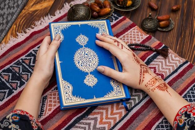日付の果物の近くにコーランを保持している一時的な刺青の人