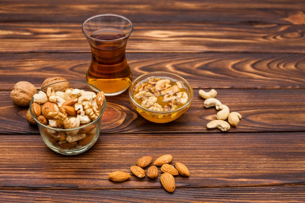 Чашка чая возле множества орехов в блюдцах
