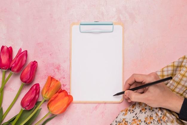 花を持つフレームクリップボードに書く人