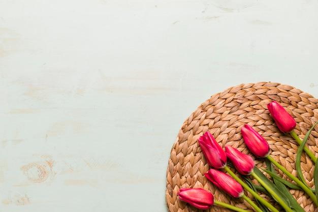 わらのマットの上のチューリップの花束