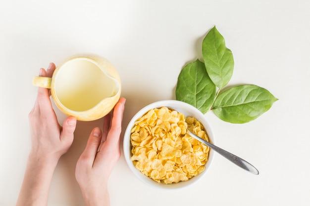 Крупным планом руки, держащей молочный кувшин; миска кукурузных хлопьев и листья на белом фоне