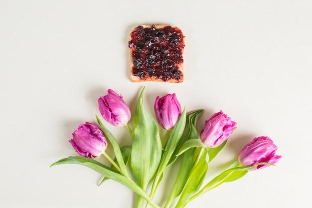 Хлеб и ягодное варенье над фиолетовыми тюльпанами на белом фоне