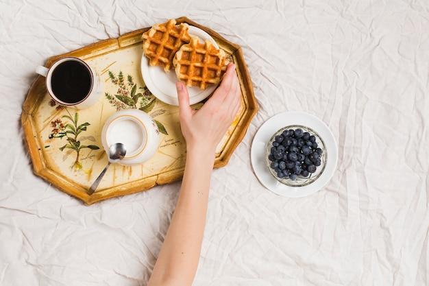 お茶とワッフルを握っている人の手のクローズアップ。粉ミルクとしわくちゃのテーブルクロスの上のブルーベリー