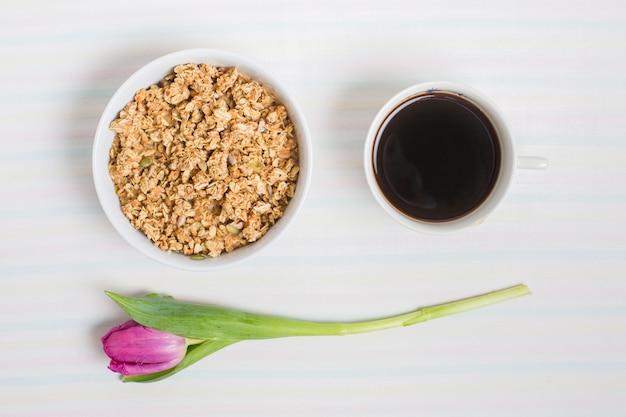 Фиолетовые тюльпаны с миской овсянки и чашка чая на белом фоне