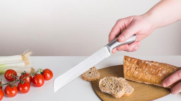 白い背景に対して白い机の上の鋭いナイフでパンを切る人のクローズアップ