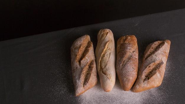 黒の背景上の焼きたてのパンに粉を振りかけた