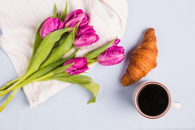 Свежие фиолетовые тюльпаны; чашка чая и круассан на белом фоне