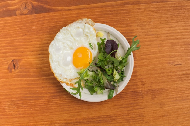サラダと半分目玉焼きの皿の上の木製のテーブル