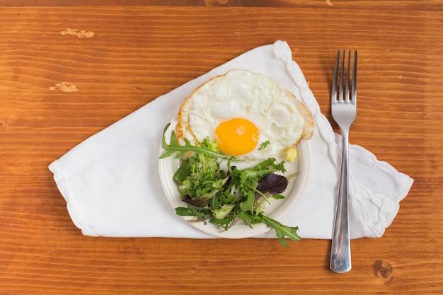 皿の上のサラダと木製の織り目加工の背景に白いナプキンの上のフォークで半分目玉焼き