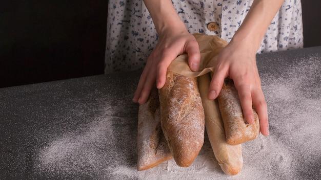 キッチンカウンターで焼きたてのパンを持っている女性の手のクローズアップ