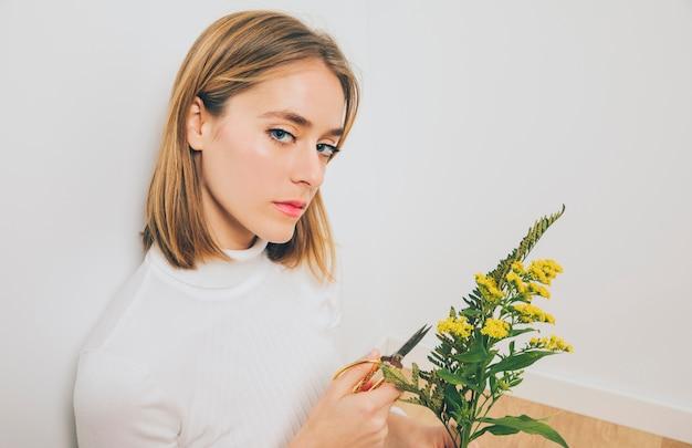 金髪の女性はさみで花を切る
