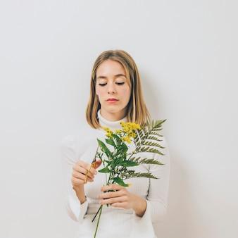 金髪の若い女性はさみで花を切る