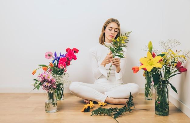 植物を床に座っていた若い女性