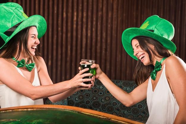 部屋の長椅子に飲み物のガラスを保持している若い女性を笑ってください。