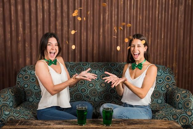 飲み物のグラスとテーブルの近くにコインを投げて幸せな若い女性
