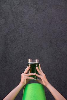 飲み物のガラスを保持している聖パトリックの帽子の女