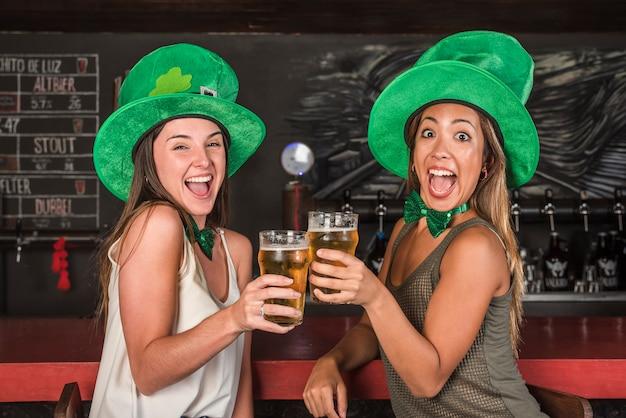 Плачущие счастливые женщины в шляпах святого патрика, звенящие бокалами с напитком у барной стойки