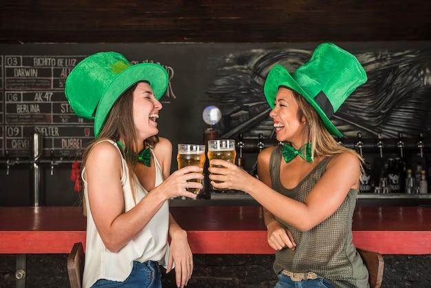 緑の聖パトリックの帽子で幸せな女性はバーのカウンターで飲み物のグラスを交換