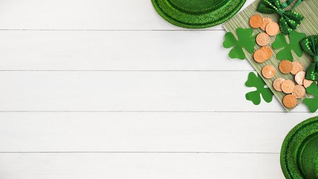 Композиция из галстуков-бабочек возле шляп, монет и зеленых бумажных клеверов на борту