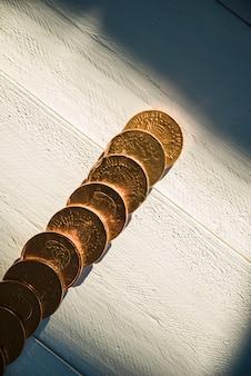 ボード上の黄金のコインと暗闇の中で太陽の光