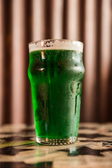 テーブルの上の冷たい緑の飲み物のガラス