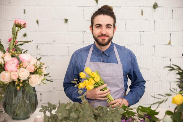 白い壁に黄色のチューリップを手で押し、男性の花屋の肖像画