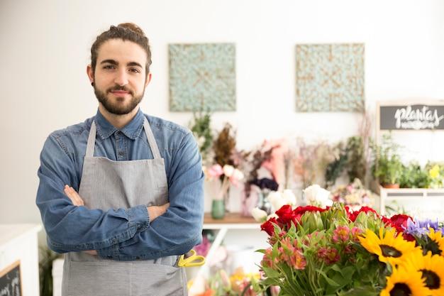 Портрет уверенно мужской флорист в своем цветочном магазине