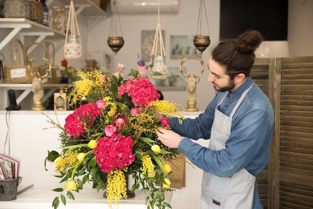 スタイリッシュな男性の花屋は店内のテーブルに花束を作成します