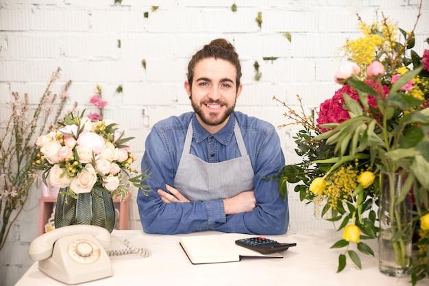 店の色とりどりの花で笑顔の若い男性の花屋の肖像画