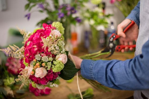 剪定鋏でカラフルな花の花束の小枝を切る男性の花屋