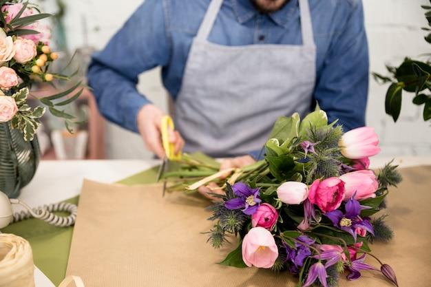 花の花束を包むための紙を切る男性の花屋のクローズアップ
