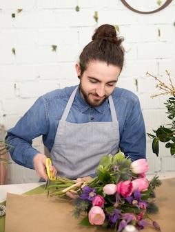 はさみで花の花束の茎を切る男性の花屋のクローズアップ