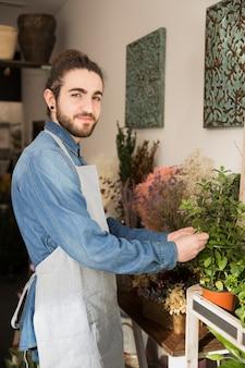 花屋で植物の世話をする若い男性