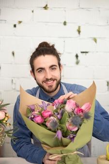 カメラを探して手に花の花束を持って若い男の肖像を笑顔