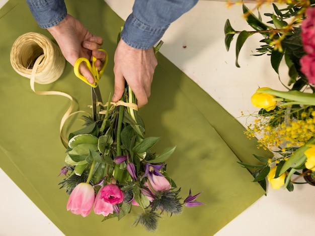 花の花束を作成する男性の花屋手の高角度のビュー