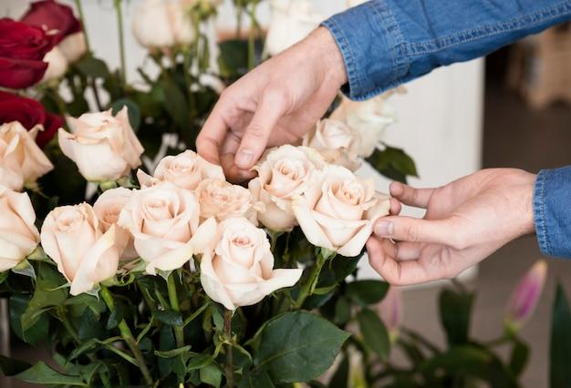 Крупный план руки человека касаясь роз