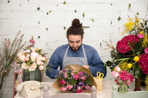 彼のフラワーショップで紙の花の花束を包む男性の花屋