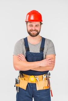 組んだ腕で立っている修理工