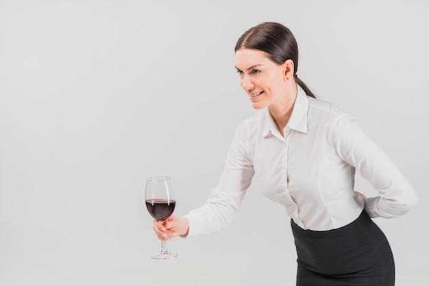 ワインのグラスを提供しているバーテンダー