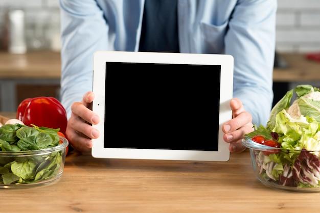 キッチンで空白の画面を持つデジタルタブレットを示す人間の手のクローズアップ