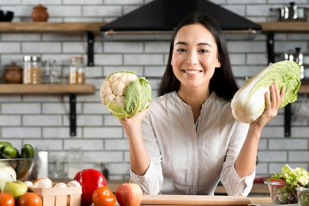 キッチンで新鮮な野菜を示す幸せな若い女