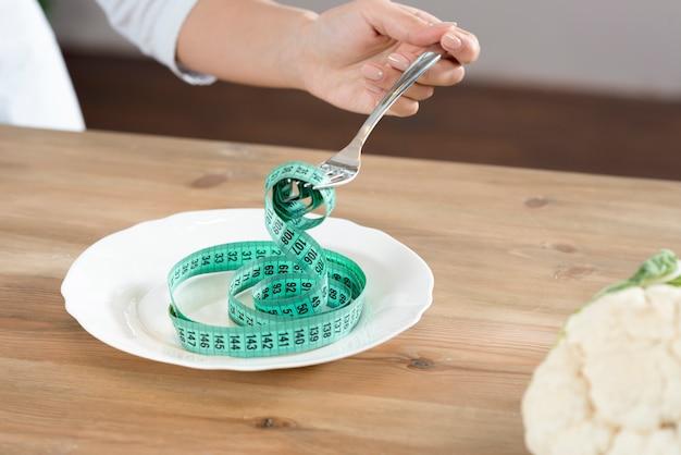 木製の机に対して白い皿に測定テープとフォークを持っている人の手のクローズアップ