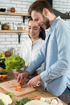 幸せなカップルが台所で一緒に食べ物を準備します。