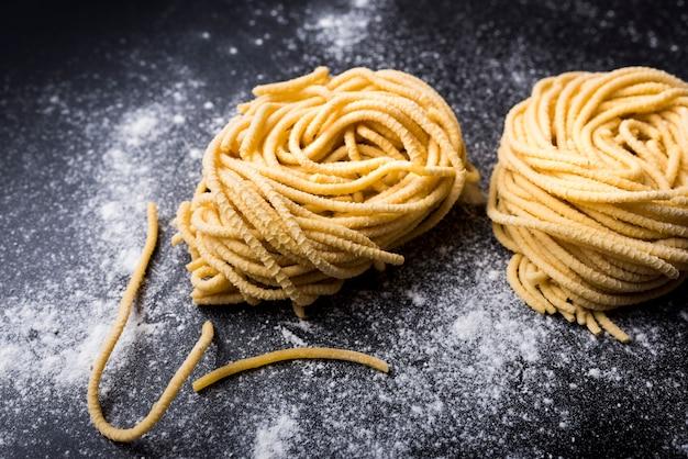黒の背景に小麦粉と生の自家製カペリーニパスタ巣