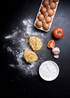 卵のカートンとカペッリーニパスタの立面図。ジューシートマト。にんにくと小麦粉のボウル