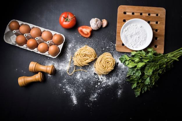 卵のカートン。野菜;小麦粉とスパゲッティパスタが黒いカウンターの上に巣を作る