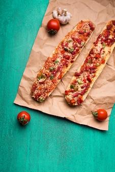 チェリートマトとターコイズブルーの背景の上にニンニクと茶色の紙の上の新鮮なおいしいバゲットピザ