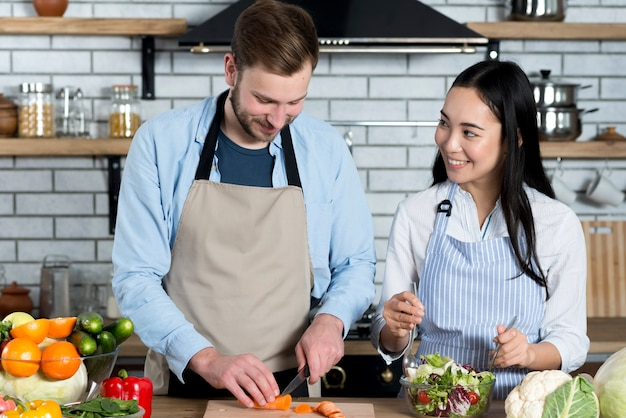 若いカップルが台所で食べ物を準備しながら楽しんで